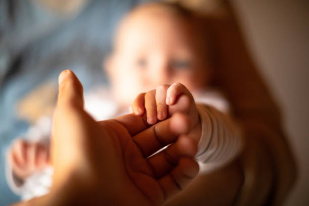 Baby reaching out toward parent